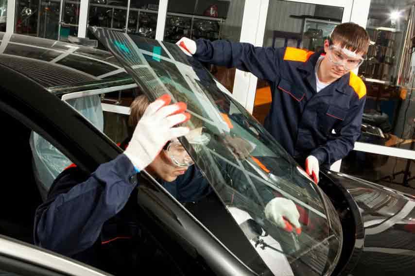 работники меняют лобовое стекло автомобиля