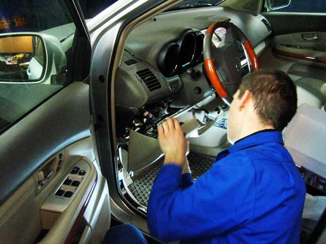 работник ремонтирует сигнализацию