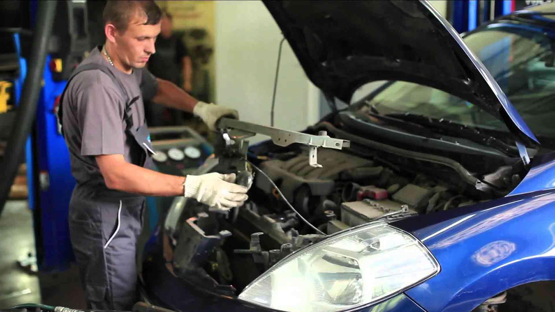 работник ремонтирует систему охлаждения автомобиля