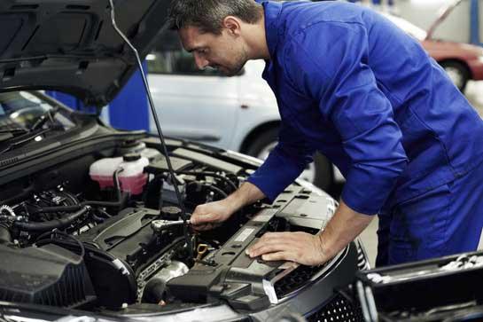 мастер меняет свечи в автомобиле