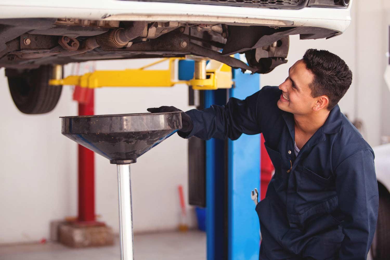 Работник сливает отработанное масло из двигателя автомобиля.