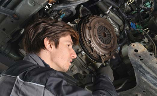 работник меняет сцепление в автомобиле